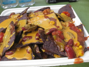 Vegan nachos with blue corn chips and tomatoes topped with queso made from peanut butter. It was so good!