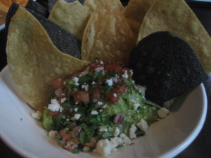 A yummy side of guacamole with chips.